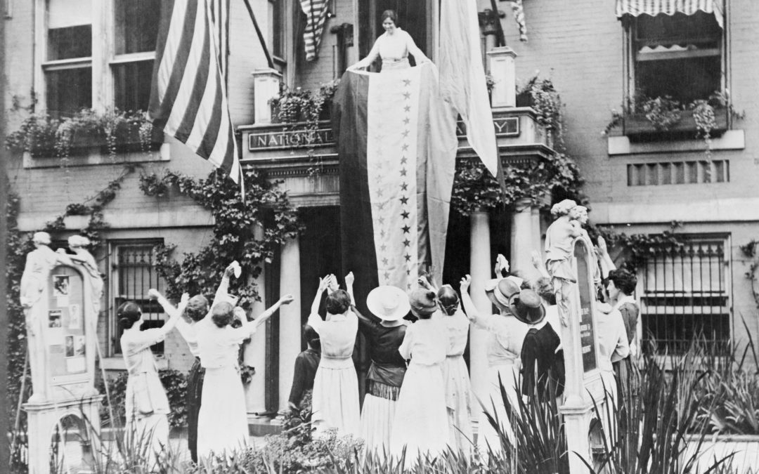 Alice Paul unfurls a banner from the balcony of the National Women's Party headquarters, celebrating the ratification of the 19 Amendment by Tennessee. Bettmann/Getty Images