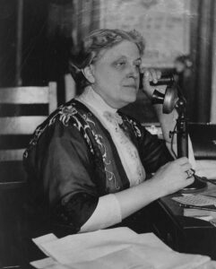 Black and white photo of Carrie Chapman Catt speaking on an old fashioned candlestick phone. LOC Carrie Chapman Catt. Collections of the Library of Congress.